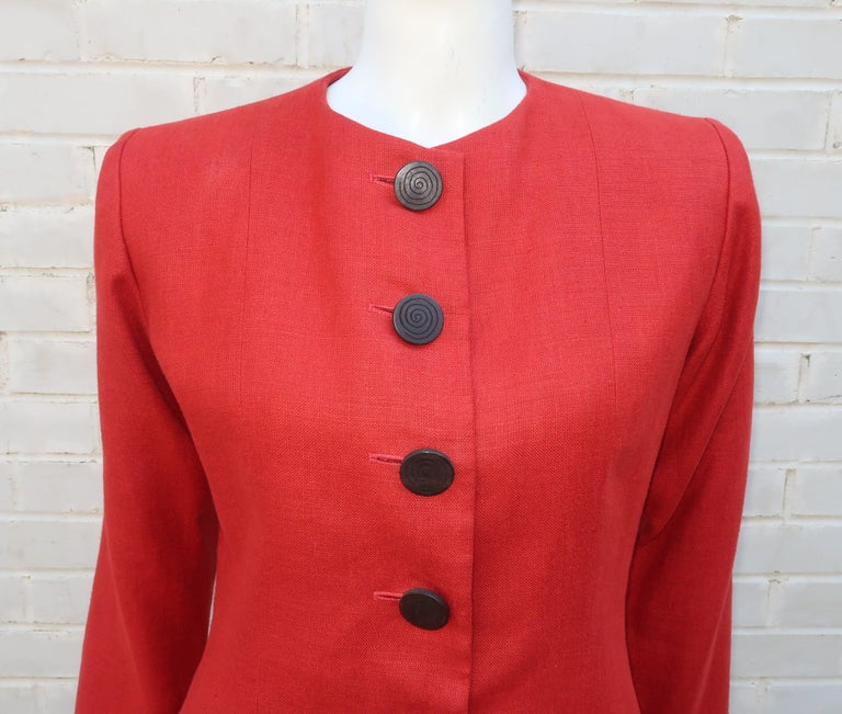 A vintage Yves Saint Laurent Rive Gauche rust orange linen collarless jacket with cutaway hemline.  The jacket closes at the front with large exotic wood buttons.  Pair it with animal or tropical prints for warm weather looks or create a safari