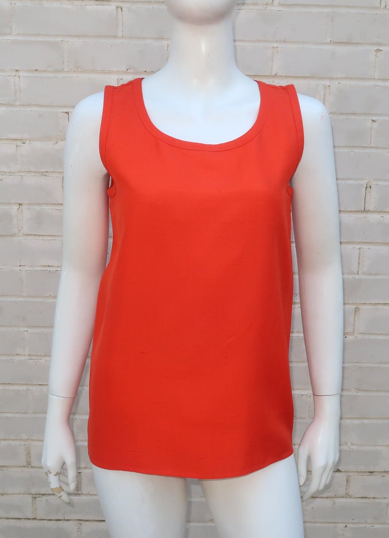 The vibrant orange shade of this simple Yves Saint Laurent Rive Gauche sleeveless blouse will add a color pop to anything and everything.  Fabricated from a beautiful nubby raw silk that offers both texture and a crisp appearance for a stand alone