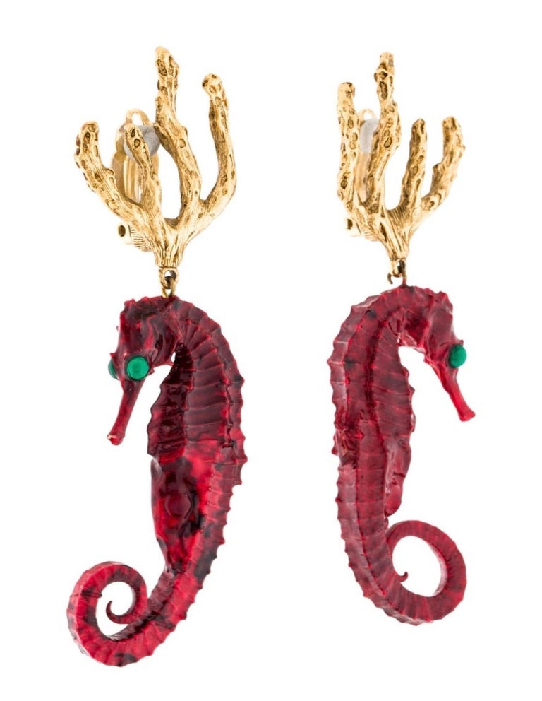 Yves Saint Laurent  vintage rare seahorse dangling clip-on earrings  featuring a gold toned coral branch top and a ruby red resin sea horse with green cabochon eyes.. Created in the ateliers of Robert  Goosens. The gold tone backs are signed YSL. In