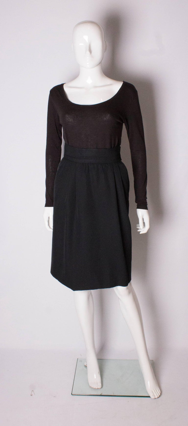 A chic vintage skirt 'Le Smoking' tuxedo  by Yves Saint Laurent Rive Gauche. The skirt is wool and fully lined, with sloping pockets and a zip on the left hand side. It has gathering on the front and ribbon detail on the left hand side.