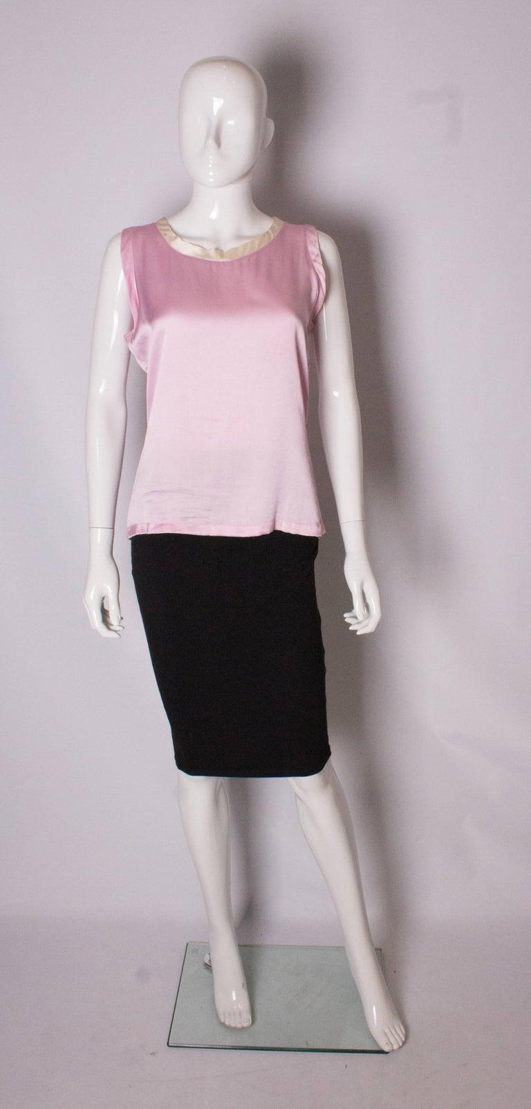 A pretty pink silk top by Yves Saint Laurent Rive Gauche. The top has a white silk trim around the neckline.