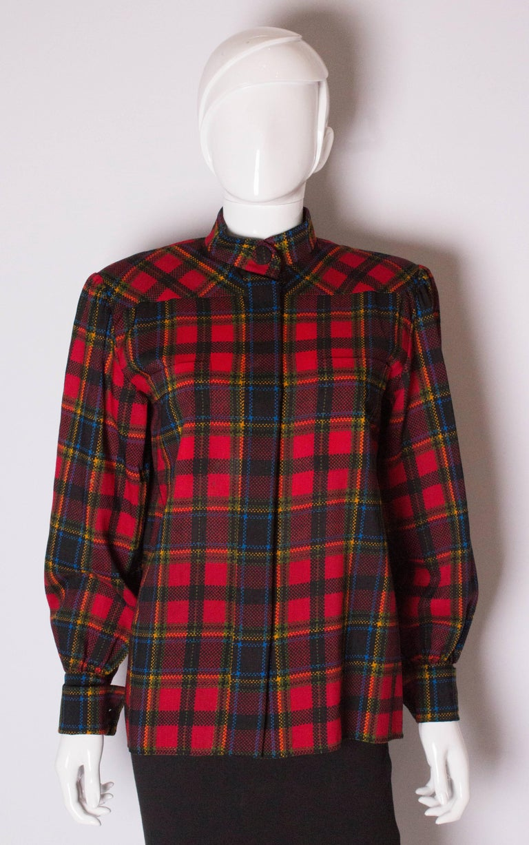 A great blouse  from Yves Saint Laurent, Rive Gauche line. The blouse has a red background , with red, blue, green and yellow lines. It has a stand up collar, one button fastening at the neck , 6 hidden button fastenings at the front and two breast