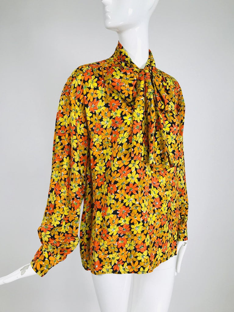 Vintage Yves Saint Laurent Rive Gauche vibrant floral silk print bow tie blouse. This beautiful silk blouse looks barely, if ever, worn. The print is bright and cheery. Pull on blouse has a button to the middle placket with attached ties at the