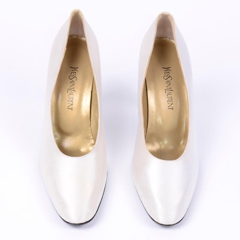 These classic Yves Saint Laurent vintage white pumps would be perfect to wear to that Summer special event or as bridal wedding shoes. These vintage YSL white satin shoes have black leather soles and were never worn. There are a few smudges on satin