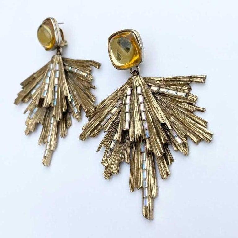 Collector! Sublime Yves Saint Laurent stud earrings in aged gold metal paved in places with rectangular rhinestones.  At the level of the attachment, a rounded dome in light yellow resin is the start of these ridged golden metal rods.  Dimensions :