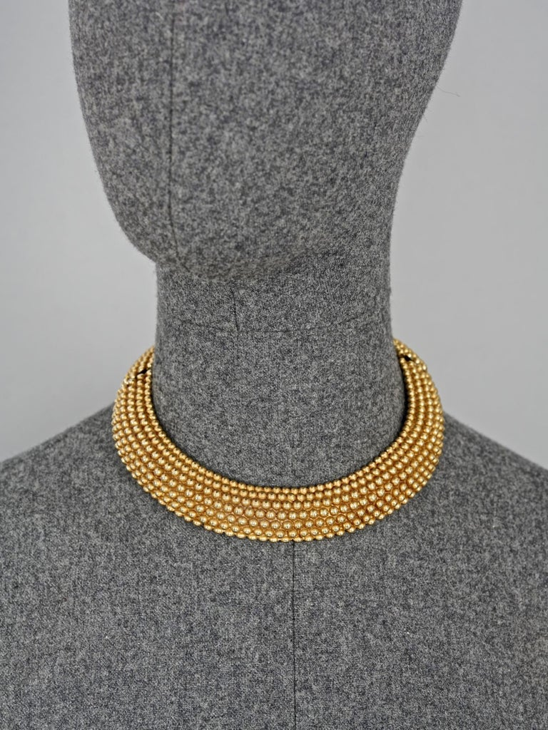 Vintage YVES SAINT LAURENT Ysl Gilt Ball Choker Necklace  Measurements: Height: 1 inch (2.5 cm) Circumference: 13.97 inches (35.5 cm)  Features: - 100% Authentic YVES SAINT LAURENT. - Gilt ball pattern rigid choker necklace. - Fold over clasp