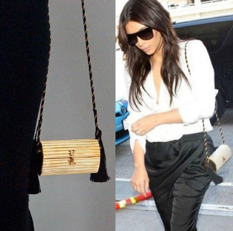 Vintage YVES SAINT LAURENT Ysl Gold Metal Minaudiere Tassel Shoulder Bag  Measurements: Height: 3.5 inches (9 cm) Width: 6 inches (15 cm) Depth: 2.55 inches (6.5 cm) Strap Length: 41 inches (104 cm) Tassel drop: 4.13 inches (10.5 cm)  As seen on Kim