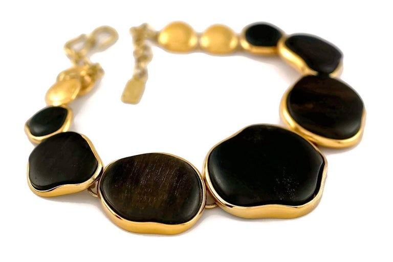 Vintage YVES SAINT LAURENT Ysl Graduated Wood Choker Necklace  Measurements: Centre Wood Medallion: 1.69inches (1.85 cm) Wearable Length: 15.35 inches (39 cm) to 17.71 inches (45 cm)  Features: - 100% authentic YVES SAINT LAURENT. - Textured