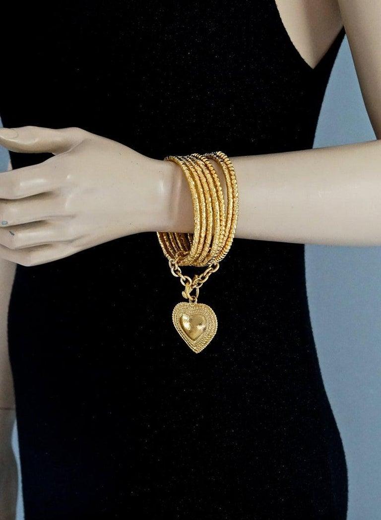 Vintage YVES SAINT LAURENT Ysl Heart Charm Stack Bangles Cuff Bracelet  Measurements: Heart Charm: 2.44 inches (6.2 cm) Stack Bangles: 3.07 inches (7.8 cm) Inner Circumference: 8.07 inches (20.5)  Features: - 100% Authentic YVES SAINT LAURENT. - 6