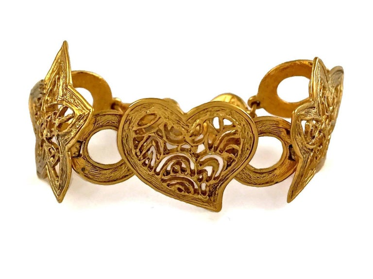 Vintage YVES SAINT LAURENT Ysl Openwork Heart Star Bracelet  Measurements: Height: 1.65 inches (4.2 cm) Length: 7.28 inches to 8.46 inches (18.5 cm to 21.5 cm)  Features: - 100% authentic YVES SAINT LAURENT. - Heart and stars link with openwork