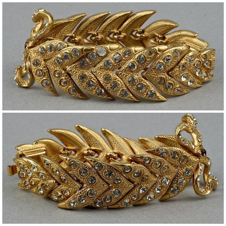 Vintage YVES SAINT LAURENT Ysl Rhinestone Bow Leaf Bracelet  Measurements: Height: 1.34 inches (3.4 cm) Wearable Length: 7.08 inches (18 cm)  Features: - 100% Authentic YVES SAINT LAURENT. - Bow centrepiece embellished with coloured rhinestone. -