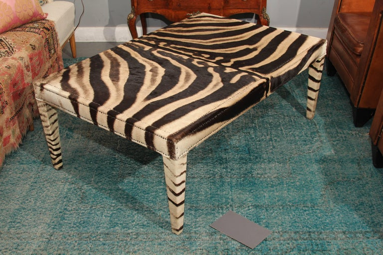 Very handsome coffee table in vintage zebra hide, trimmed in small nailheads.