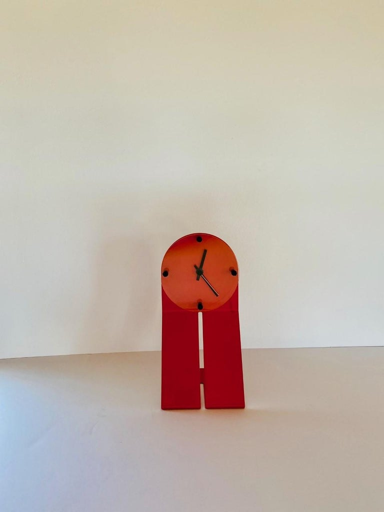 Graphic and high design piece by Seccose. The metal frame is bent to create an effect on profile. The piece is powered coated in a unique orange red color, finished with a plexiglass circle that protects the quartz time mechanism. This piece was