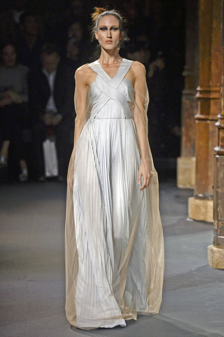 Vionnet of Paris veraline blue plisse pleated cutout gown is the 1st look that opened the 2016 Spring runway show. (see photo)  Sleeveless with pleated panels of bodice twisted together extending into a lightly gathered fully pleated long skirt.