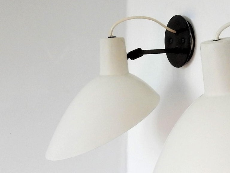 This stunning wall lamp was designed by Vittoriano Vigano for Arteluce in Italy in the 1950s. This model is often named 'Visor'. The lamp is adjustable in all directions or in a set position. It has the original label of Arteluce on the inside. The