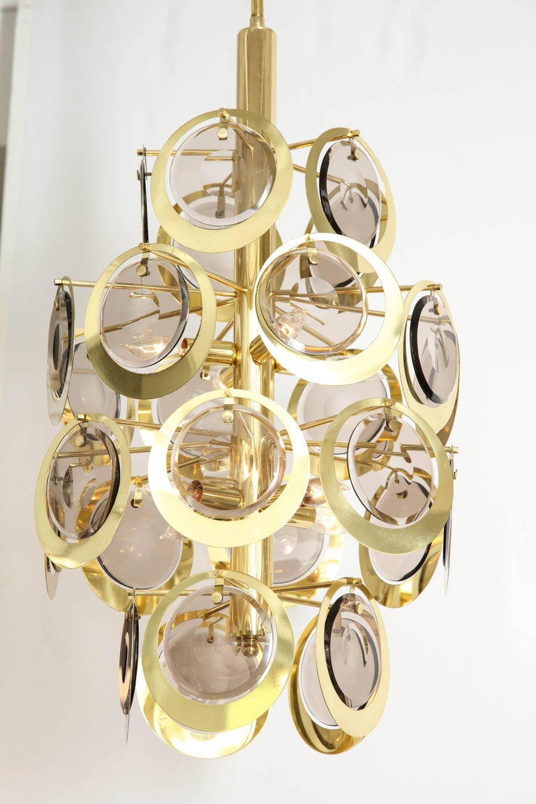 This Vistosi attributed chandelier with 28 Murano glass and brass discs was made in the 1970s. The brass frame has eight lights that have been recently re-wired for the US (40 watt max per socket).