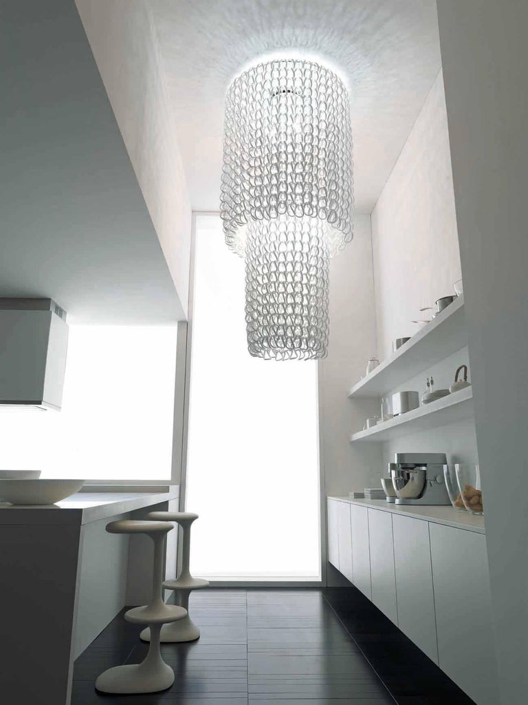 The Giogali collection is a decorative lighting system based on a single element: the handmade glass link. Featured Cascade chandelier in crystal. Metal parts in chrome. E26 lighting.