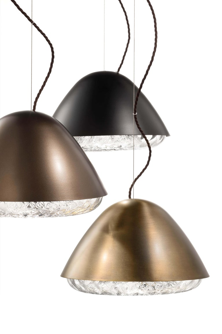 Kira is a collection of lamps combining metal with blown glass. The result is a set of lighting systems composed of two antithetical halves: a diffuser in crystal glass, decorated and embellished with a rich surface texture, topped with a turned