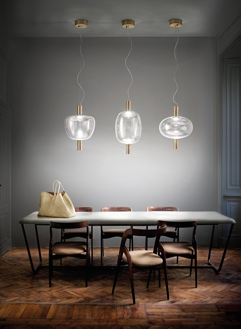The LED light passes through a glass bubble to refract on a mirror in a game of continuous rebounds. Glass is not only a diffuser, but also an almost invisible intermediary between the light source and the reflecting element. The simplicity and
