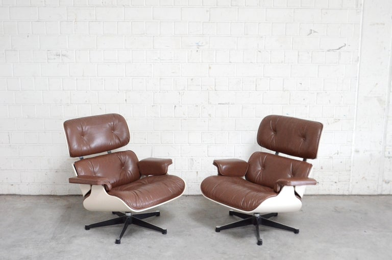 2 similar Vitra Eames lounge chairs. Original Cognac brown Seminaniline leather. It was lacquered in white from a professional company. Very good condition.