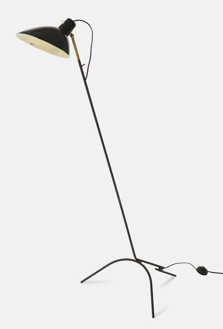 Designed by Vittoriano Vigano and manufactured by Arteluce in Italy, circa 1951, rare and original floor lamp model 1047 with black lacquered aluminum adjustable shade on brass stem and tripod base, with original manufacturer's label inside the