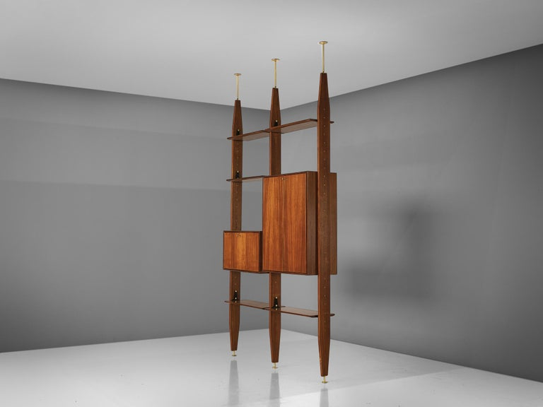 Vittorio Dassi, wall unit book shelf, in Brasillian hardwood and brass, Italy, 1960s.  This book shelf features a three legged structure that can freely be fixed between the ceiling and the floor. In between the legs the shelves and storage space