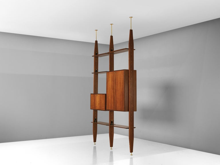 Vittorio Dassi, wall unit book shelf, in walnut and brass, Italy, 1960s.  This book shelf features a three-legged structure that can freely be fixed between the ceiling and the floor. In between the legs the shelves and storage space are adjustable