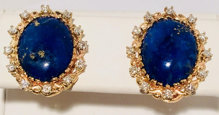 Traditional, classic earrings feature large, vivid blue, oval cut lapis lazuli stones with rich gold flecks, surrounded by sparkling, yellow gold, prong set round brilliant diamond halos in post settings with friction backs for pierced ears.   2