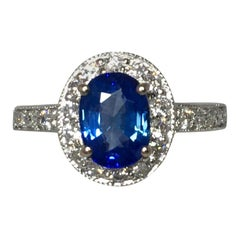 Vivid Blue Sapphire and Diamond 18 Karat White Gold Oval Cut Halo Cluster Ring