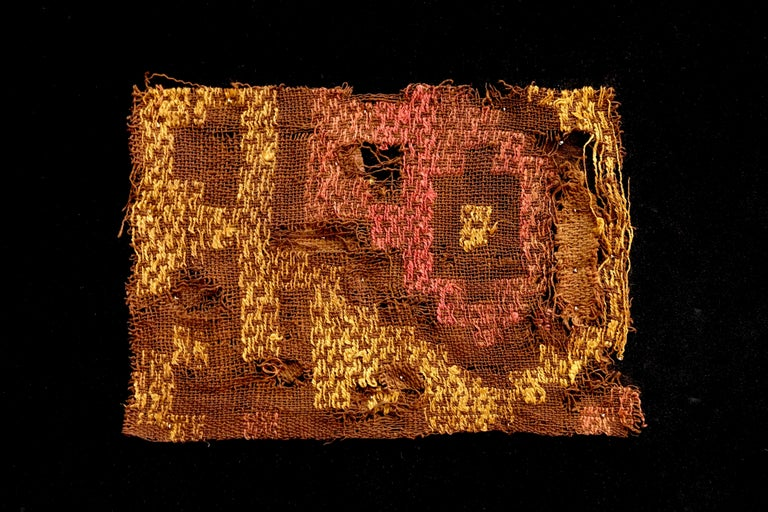 Bright yellow and pink in geometric arrangements adorn this brown pre-Columbian textile fragment.? Framed in a black shadow box.