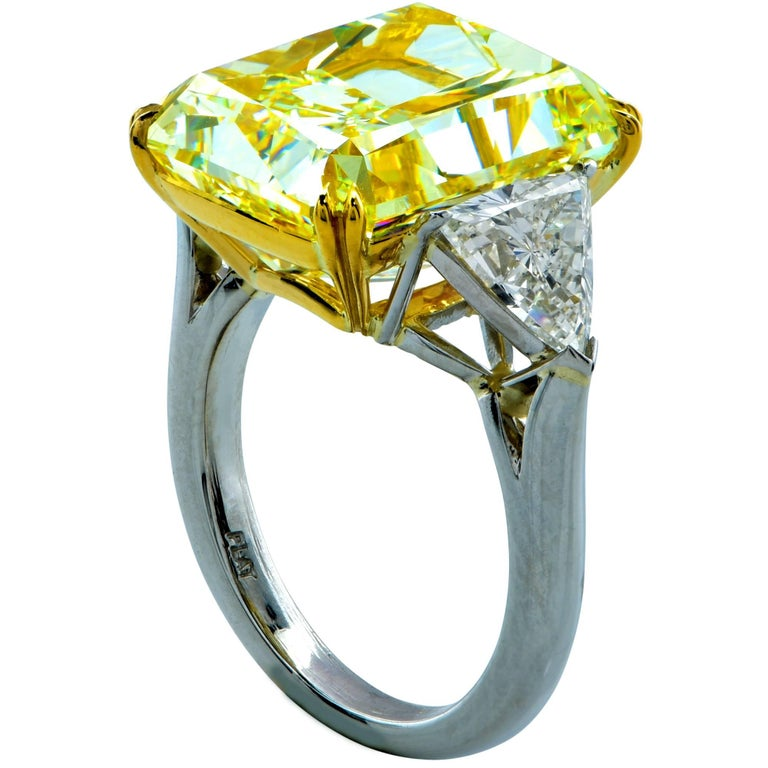 This alluring three stone diamond engagement ring features a GIA graded 14.20ct fancy light yellow radiant cut diamond with VS2 clarity. This beautiful diamond has incredible saturation of color and immaculate scintillation. It is masterfully