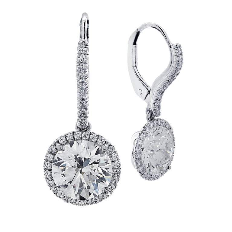 Sensational Vivid Diamonds dangle earrings crafted in 18 karat white gold showcasing two round brilliant cut diamonds weighing 3 carats total, I color, I1 clarity framed in diamond halos and suspended from diamond encrusted posts. 70 round brilliant