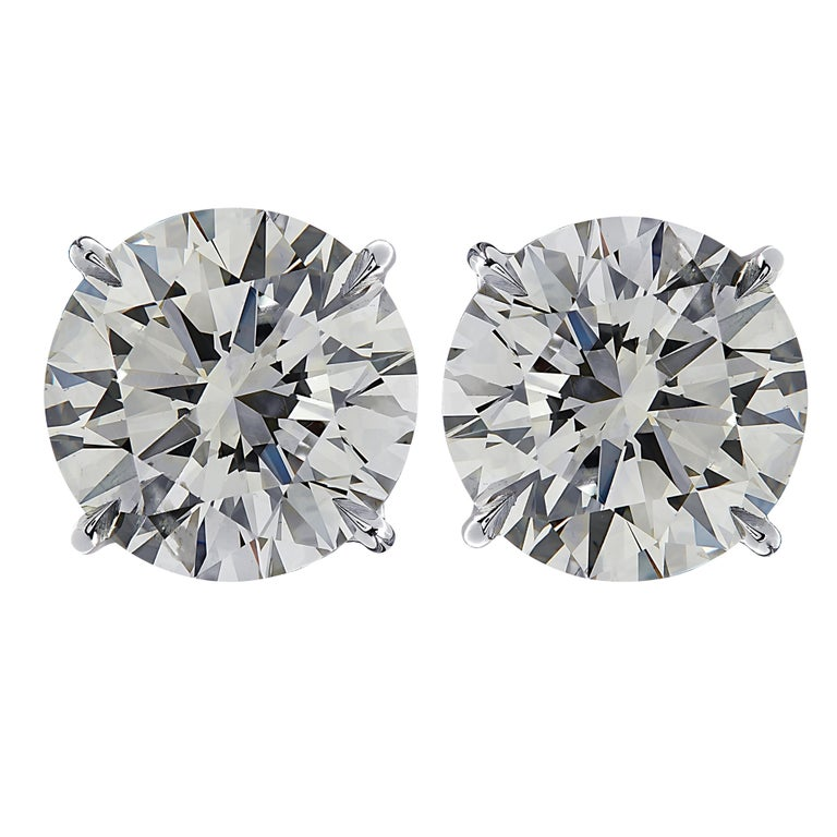 Stunning Vivid Diamonds solitaire stud earrings crafted in 18 karat white gold, showcasing 2 spectacular round brilliant cut diamonds weighing 8.14 carats total, I-J color SI clarity. These diamonds were carefully selected and perfectly matched to