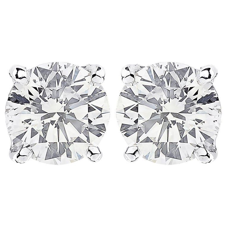 Stunning Vivid Diamonds solitaire stud earrings crafted in 18 karat white gold, showcasing 2 spectacular GIA Certified round brilliant cut diamonds weighing 2.06 carats total, L color SI1 clarity. These diamonds were carefully selected and perfectly