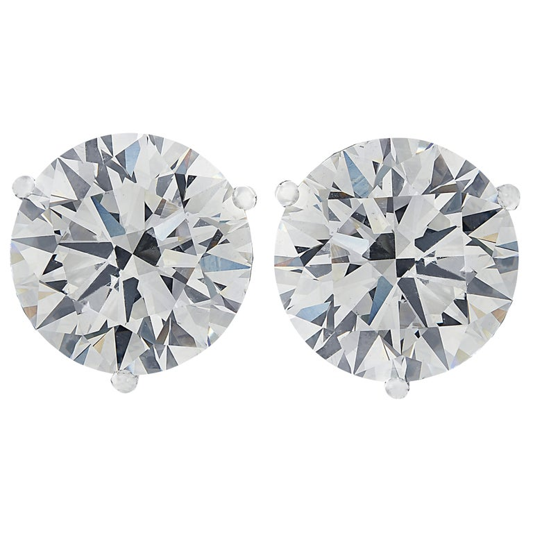 Stunning Vivid Diamonds solitaire stud earrings crafted in 18 karat white gold, showcasing 2 spectacular round brilliant cut diamonds weighing 8.13 carats total, J color SI1 clarity. These diamonds were carefully selected and perfectly matched to