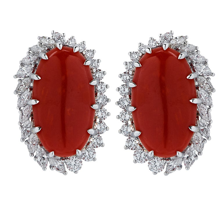 Spectacular earrings crafted in 18 karat white gold featuring two ox-blood coral cabochons framed in 24 round brilliant cut diamonds, G color, VS clarity and 24 marquise cut diamonds weighing 2 carats total, G color, VS clarity. These stunning