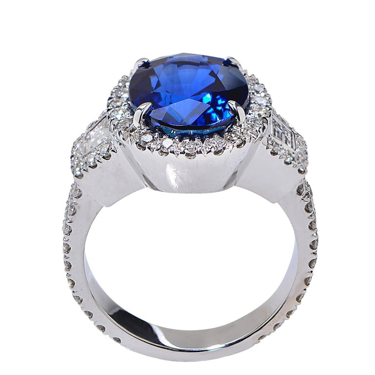 18 Karat White Gold Ring Featuring a 6.22 Carat Natural Blue Sapphire from Madagascar, Heated, AGL Certified, Accented by 1.16 Carats of Trapezoid and Round Brilliant Cut Diamonds, G Color, VS Clarity.  Ring Size: 6 Weight: 11.69 grams  This