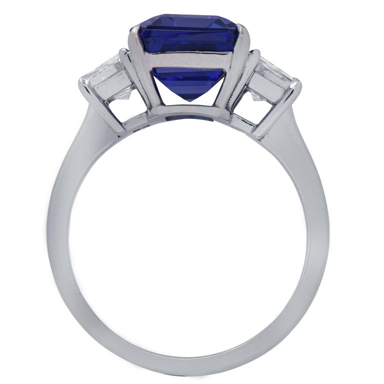 Spectacular Vivid Diamonds ring, handcrafted in Platinum featuring a 4.29 carat Emerald Cut Tanzanite adorned with 2 step cut trapezoid diamonds weighing .94 carats total, F color and VS clarity. The band of this stunning ring measures 2.2 mm 2.67