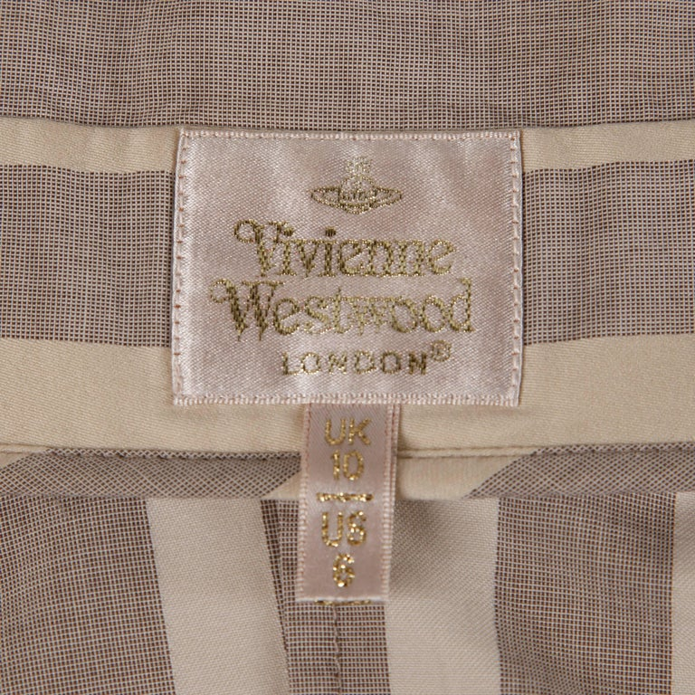 Chic gray and beige striped button up blouse by Vivienne Westwood! Avant garde neck and shoulder cut and rarer gold label. Love the logo embossed on the top button!  Details:   Unlined Button Front Closure Marked Size: UK 10/ US 8 Color: Gray/