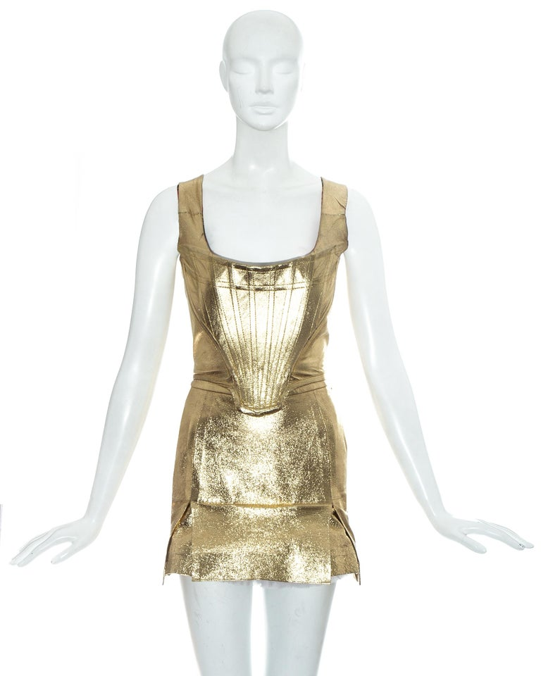 Vivienne Westwood; gold leather corset and skirt ensemble. Corset with internal boning, designed to cinch the waist and push the breasts up. High waisted mini skirt designed backwards with vent at the front and tulle petticoat.     Time Machine'