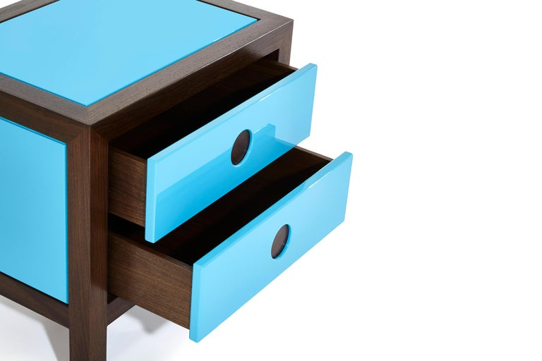 Mixing midcentury shapes with glossy lacquer, richly stained walnut, and inset circular walnut details, these single push to open drawer nightstands are the perfect mix of function and high style.