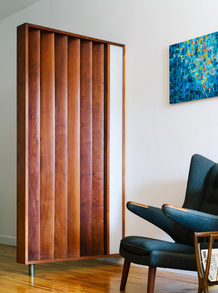 An incredibly rare louvered and illuminated room divider in solid walnut floating over a cylindrical brass foot, custom-designed by Vladimir Kagan circa 1967. Six sculptural, marquise-shaped slats are angled at 45 degrees to the frame and flank the