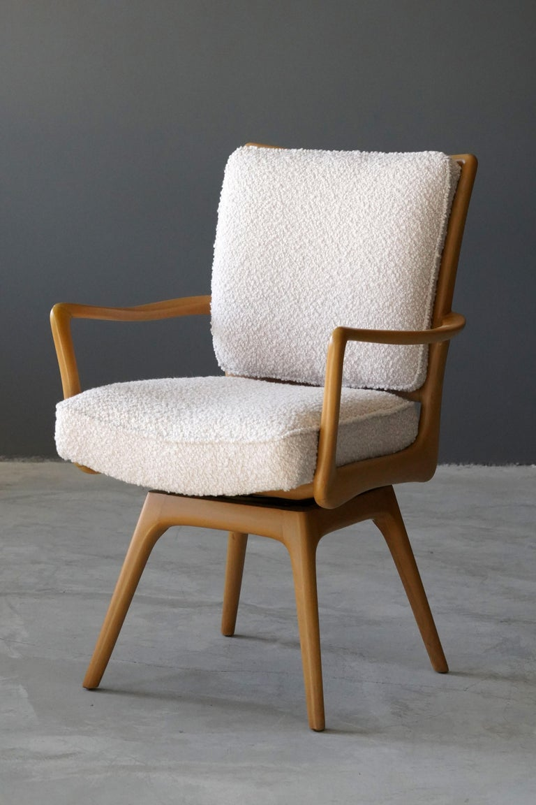 A swiveling organic armchair / desk chair designed by Vladimir Kagan. Organically carved wood is paired with a high-end bouclé fabric. Produced by Kagan-Dreyfus, 1960s. With metal plaque.  Other designers of the period include Paul Frankl, Gio