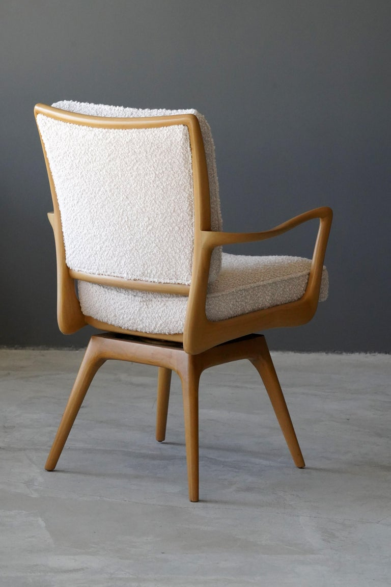 A swiveling organic armchair / desk chair designed by Vladimir Kagan. Organicly carved wood is paired with a high-end bouclé fabric. Produced by Kagan-Dreyfus, 1960s. With metal plaque.   Other designers of the period include Paul Frankl, Gio