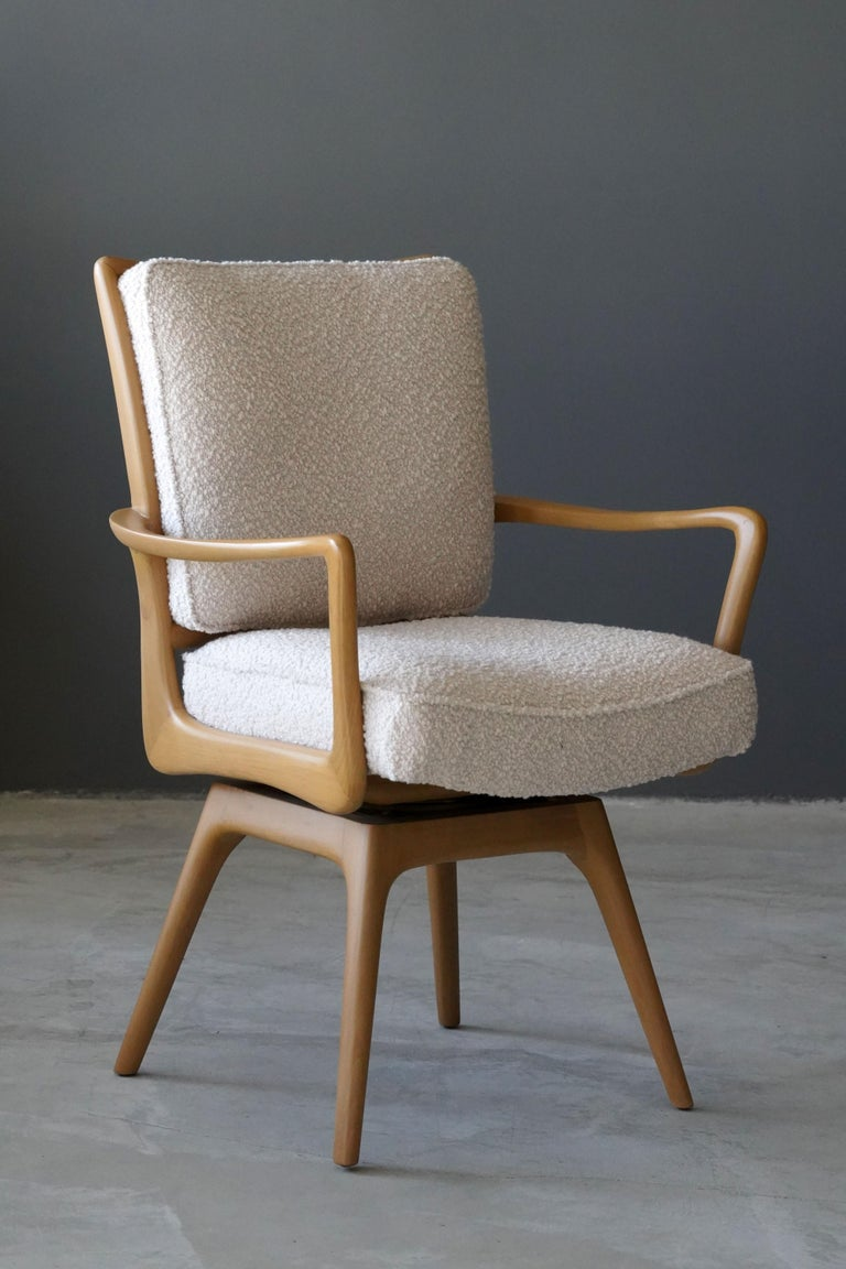 A swiveling organic armchair / desk chair designed by Vladimir Kagan. Organically carved wood is paired with a high-end bouclé fabric. Produced by Kagan-Dreyfus, 1960s. With label.  Other designers of the period include Paul Frankl, Gio Ponti,