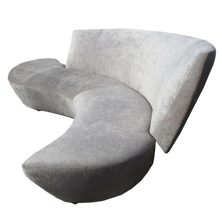 This undulating serpentine sofa was inspired by Frank Gehry's Bilbao Museum of Spain. Kagan combined angular and curved forms to create a unique design in seating luxury. We have re-upholstered the sofa in a taupe chenille fabric shot with silver