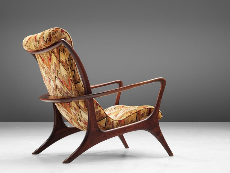 Vladimir Kagan for Dreyfuss, 'Contour' high back chair, teak and fabric, United States, 1953  This lounge chair by Kagan is sculptural and delicate. The frame, executed in teak and carved in an exquisite manner. The hind legs are long and protrude