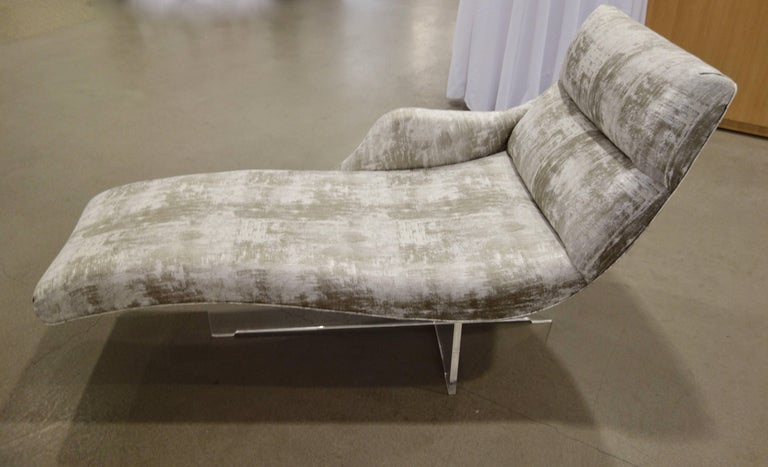 "Vladimir Kagan's ""Erica"" chaise lounge, named after his wife, features a right sided armrest with an undulating, tapered body floating on a bisected lucite base, newly upholstered in mottled greige slightly puckered fabric with a glints of metallic"