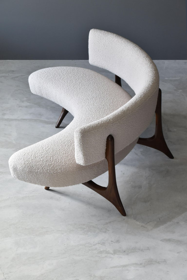 A hyper-modern and organic sofa designed by Vladimir Kagan in 1952. Produced by Vladimir Kagan Designs, Inc, circa 1980. Executed in finely sculpted walnut, overstuffed seat and back have been restored and reupholstered using a high-end bouclé