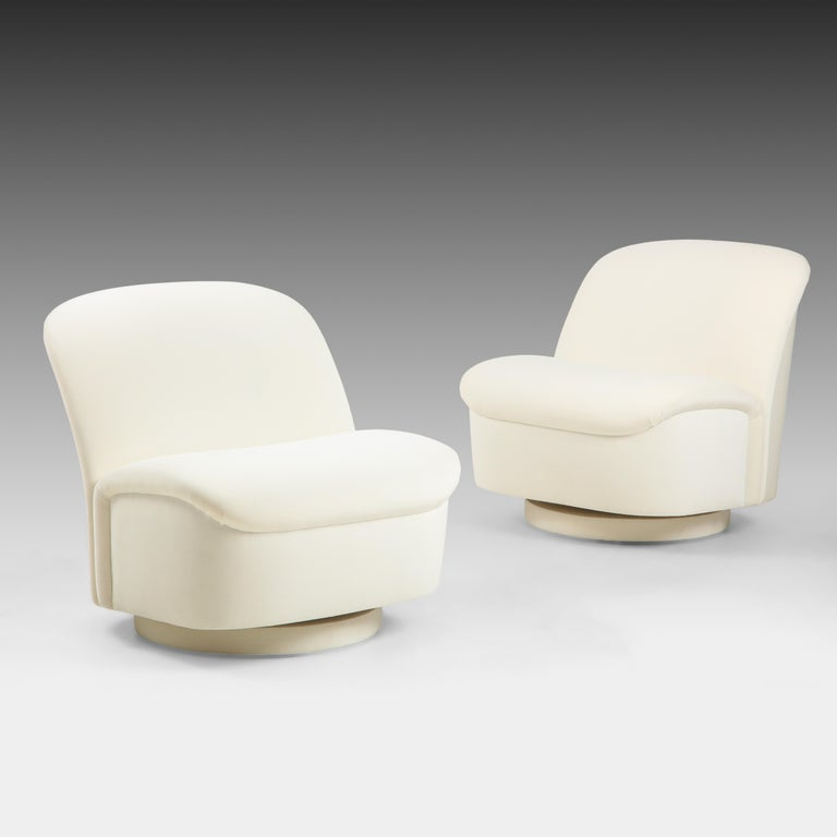 Vladimir Kagan for Directional pair of ivory velvet swivel lounge chairs with slightly curved backs and seats which tilt back and forth and swivel on upholstered round base. These chic swivel lounge chairs are not only beautifully sculptural but